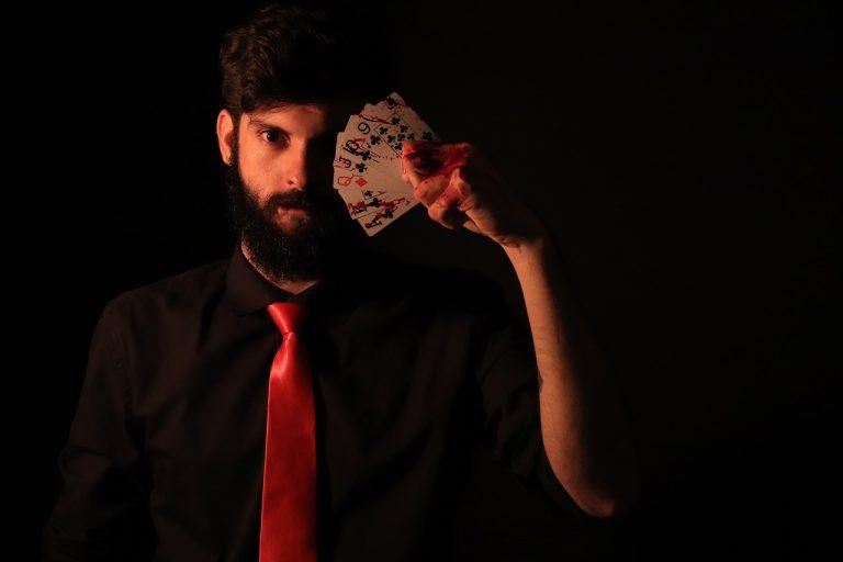 איש עם זקן שחור ועניבה אדומה מחזיק עשרה קלפים