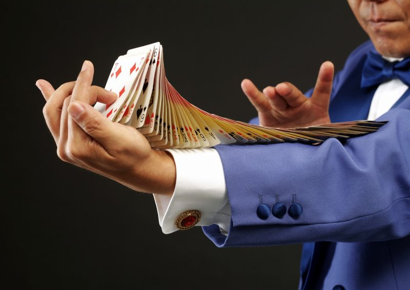 איש עם חליפה כחולה מערבב חפיסת קלפים על הזרוע